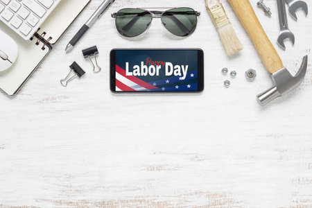 Table top view of labor day abstract background concept. Flat lay mockup smartphone with Happy Labor Day USA Holiday and essential worker tools on grunge white wood background with copy space.