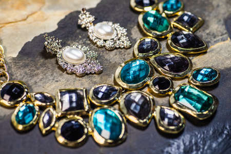 Pearl earrings and gemstones pendant, Traditional jewellery. Beautiful vintage female jewellery on dark stones background. Selective focus. Reklamní fotografie