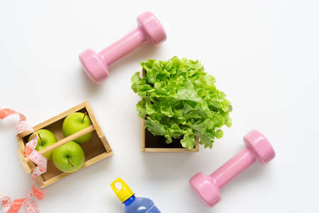 Flat lay workout and fitness dieting healthy lifestyle with healthy food green apples and green lettuce, pink dumbbels, bottle of water and measure tape. Reklamní fotografie