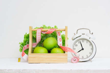 Healthy time and dieting concept. Vintage retro alarm clock and green apples and lettuce in  wood basket on grunge white wooden table. Wellness and healthy  lifestyle concept.