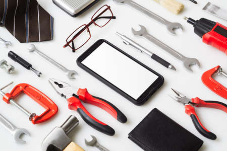 Flat lay mock up Smart Phone With mans accessories and essential construction tools worker on white background. Mockup mobile phone for your advertisement artwork. Reklamní fotografie