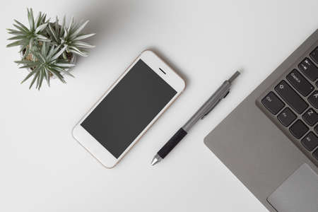 Mobile phone mockup, top view of White office desk table with mockup blank screen smartphone and computer laptop. Flat lay top view Office desktop with smart phone for mock up.