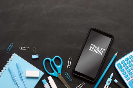 Mock up mobile phone for back to school background concept. School items on grunge black chalkboard texture background with mockup smartphone for your artwork.