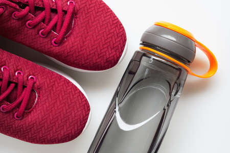 Red sport shoes and bottle of water. Active healthy lifestyle background concept. Fitness and wellness healthy living, dieting background.