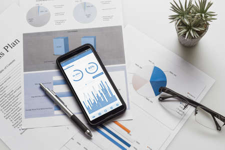 Top view of office desk table with graph chart on mock up smartphone on white desk table. Business management via mobile application concepts ideas. Mock up mobile phone for your Advertisement.