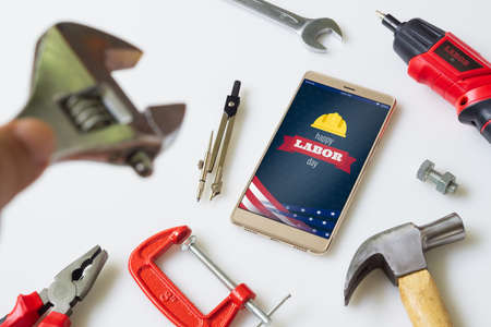 Happy labor day background concept. Flat lay mobile Phone With Happy Labor Day USA Holiday and essential construction tools worker on white background. Top view Mock up mobile phone.