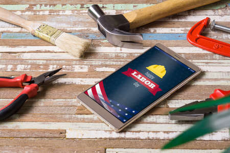 Happy labor day background concept. Flat lay mobile Phone With Happy Labor Day USA Holiday and essential construction tools worker on grunge wood background. Top view Mock up mobile phone.