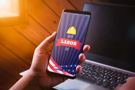 Happy Labour day mockup mobile phone concept. Close up business woman hand holding smart phone with Happy Labor Day on screen with blurred laptop background. Imagens