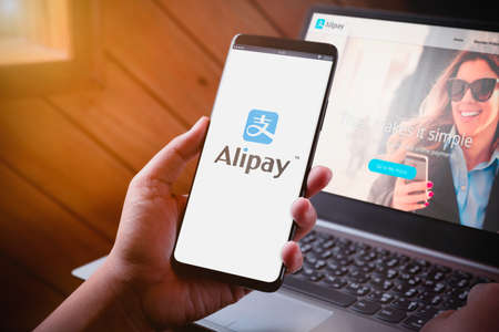 Bangkok, Thailand - August 5, 2019: Hands holding Smartphone with Alipay logo on screen and Alipay website on laptop background. Alipay is mobile and online payment platform, established by Alibaba group. Stock Photo - 133575449