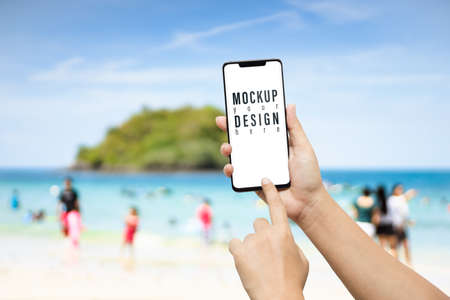 Mockup image of a hand holding and showing modern mobile smart phone  in front of the beach in summer with may tourist and blue sky background Stok Fotoğraf