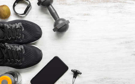 Fit and Healthy lifestyle background concept. sport shoes, smart mobile phone, dumbbell, smart watch, bottle of water on grunge white wood. Top view flat lay style. Archivio Fotografico - 129272501