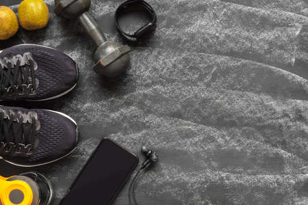 Fit and Healthy lifestyle background concept. sport shoes, smart mobile phone, dumbbell, smart watch, bottle of water, kiwi fruit on grunge black chalk board. Top view flat lay style. Archivio Fotografico - 129272525
