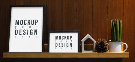 Blank mockup frame on wall shelf. Mock up blank white picture frame on wooden shelf in the living room. Zdjęcie Seryjne