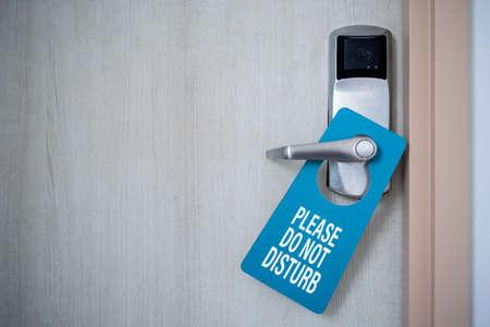 Closed door of hotel room with please do not disturb sign. Hotel Door Hanger Tags Mockup.