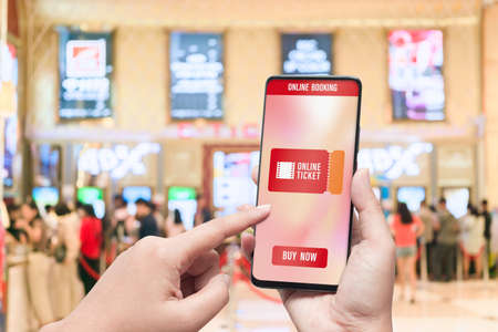 Mockup mobile phone hand using smartphone to buy cinema tickets with blurred image of ticket sales counter at movie theater with graphic icon, online booking and payment concept Stock Photo