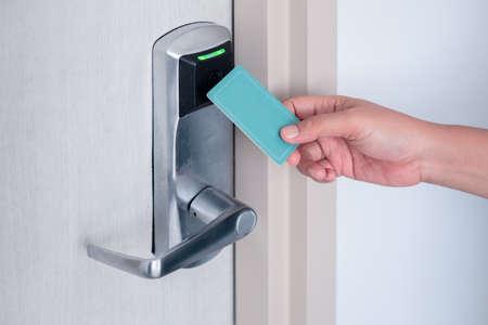 Hand met behulp van elektronische slimme contactloze sleutelkaart voor het ontgrendelen van de deur in hotel of huis.