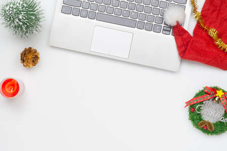 Flat lay top view Christmas office table desk party concept, Christmas workspace with laptop, Santa Claus hat and Christmas decorations on white background Stock Photo
