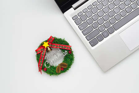 Merry Christmas and Happy new years office work space desktop concept. Flat lay top view with laptop and Christmas ornaments sign with copy space. Stockfoto