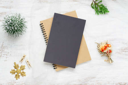 Top view of blank cover notebook on nest fabric and white wood  background with xmas decorations. Mockup Christmas background with notebook for wish list or to do list. Flat lay with copy space.