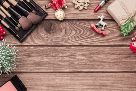 Woman cosmetics, makeup brushes, lipstick and Christmas ornaments on wood background, Flat lay top view with copy space. Christmas time and New year cosmetics background concept.