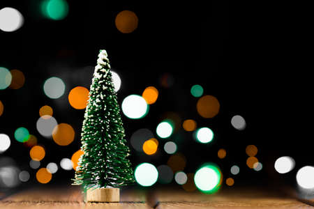Christmas decorations on a wooden table with glowing lights. A small artificial Christmas tree with light bokeh background. Archivio Fotografico - 132247195