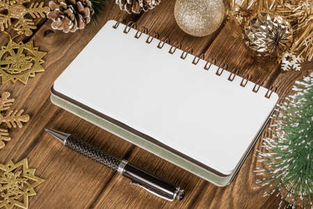 Blank notebook on  wood background with Christmas ornaments decorations. Mockup Christmas background with notebook for wish list or to do list. Copy space for your text.