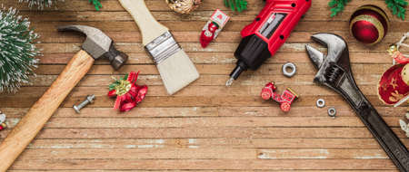 Merry Christmas and Happy New Years Handy Constrcution Tools web banner background concept. Handy House Fix DIY handy tools with Christmas ornament decoration on a rustic wooden table.