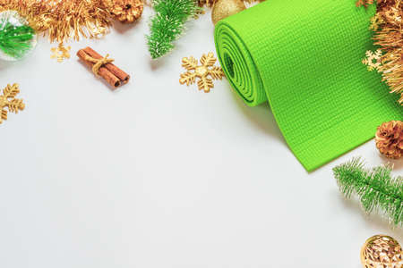 Green yoga mat or pilates mat with Christmas ornaments decoration. Christmas best gift for healthy lifestyle people concept. Yoga xmas and happy new year background. Copy space.