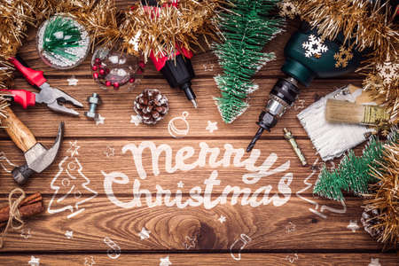 Merry Christmas and Happy New Years Handy Construction Tools background concept. Handy House Fix DIY handy tools with Christmas ornament decoration on a rustic wooden table. Industrial Xmas Background.