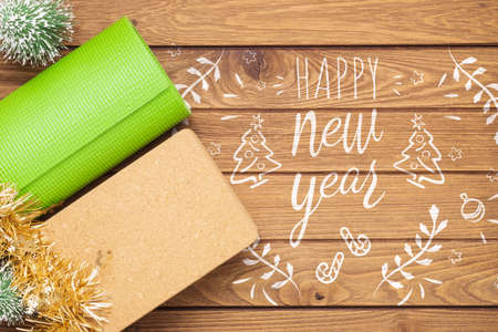 Green yoga mat or pilates mat and  block with Christmas tree ornaments decoration on wood for Merry Christmas and Happy new year background concept