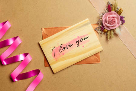 Wooden card with I love you text and envelop on brown craft paper with kraft paper roses for Valentines Day. Mock up for elegant design. Flat lay top view valentines day background concept.