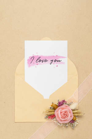 Mockup card and envelop on white wood with I love you text and kraft roses for Valentines Day. Mock up for elegant design. Flat lay top view valentines day background concept.