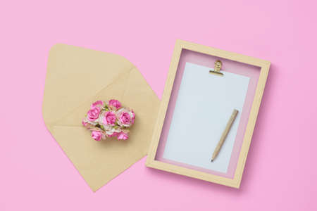Mockup photo frame with kraft rose flower in brown envelope for Valentines day concept Stock Photo