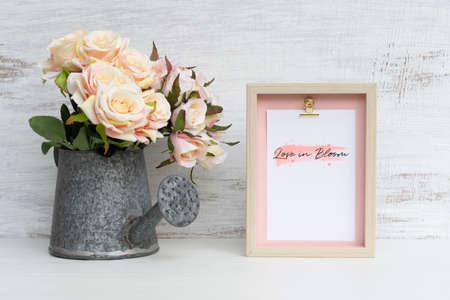 Mockup Still life Cadre photo et arrosoir avec Bouquet de roses sur bois blanc grunge. Concept de fond de Saint Valentin. Maquette avec cadre photo pour votre photo ou texte