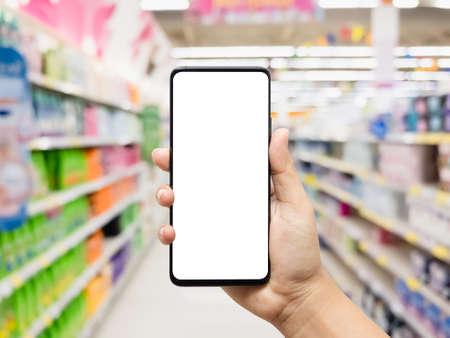 Main tenant un smartphone avec un supermarché flou Banque d'images