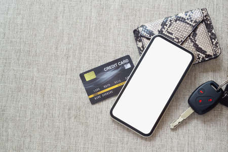 Mockup blank screen mobile phone for online payment and Car rental online application background concept. Mock up white screen cellphone with credit card, car key, wallet, top view, flat lay