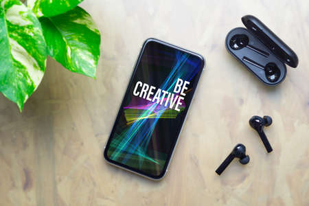 Be creative inspirational background concept. Flat lay top view of Be Creative text on Smartphone with Wireless earphones and charging case on working office desk.