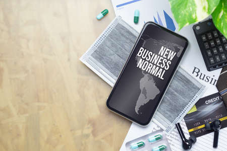 The Business New Normal After Covid-19 background concept. A smartphone with new business normal message with world map, medical face mask, medicine tablet  on businessman working desk.