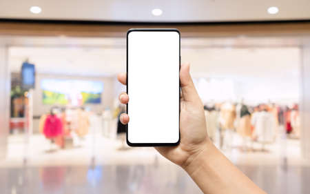 Mockup blank white screen mobile phone. Hand holding smartphone wirh blurred clothing store background for your text or advertisement artwork.
