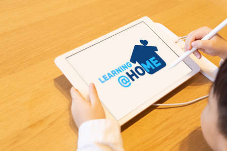 Leaning at Home background concept. Schoolboy Kit at home using tablet when studying at home. Kid make homework on quarantine. Mockup tablet on the table at home.