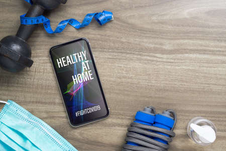 Healthy At home for quarantine times in Coronavirus Covid-19 pandemic outbreak background concept. Mockup mobile phone for fit and workout at Home, Be Active during virus pandemic.