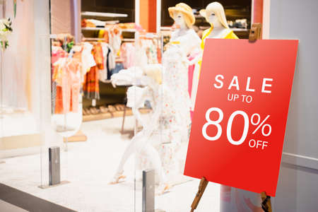 Sale label billbord stand template in front of female clothing store for sale promotion and discount information for Black Friday and Holiday season sale. Sale Banner template mockup. Discount sale up to 80% red sign in shopping mall.