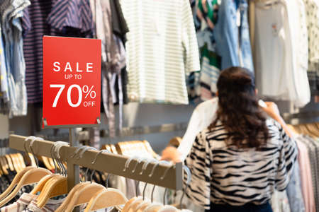 Sale label stand template on shelve in female clothing store for sale promotion and discount information for Black Friday and Holiday season sale. Sale Banner template mockup. Discount sale 70% red sign in shopping mall.