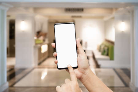 Mockup blank white screen smartphone hand pointing and touch mobile phone isolated on white with blurred background of beautiful living room, blank screen cellphone mock up for your  advertisement.