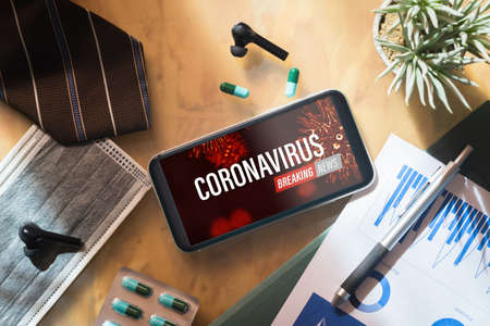 Coronavirus or Covid-19 outbreak Breaking News update background concept. Mockup mobile phone with facial masks and medical tablets on businessman's office wood desk table. Stockfoto