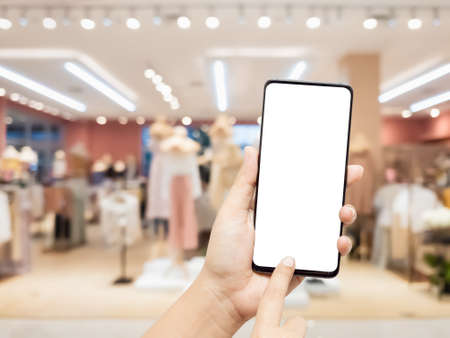 Mockup blank white screen mobile phone. Hand holding and pointing to smartphone wirh blurred female clothing store background for your text or advertisement artwork.