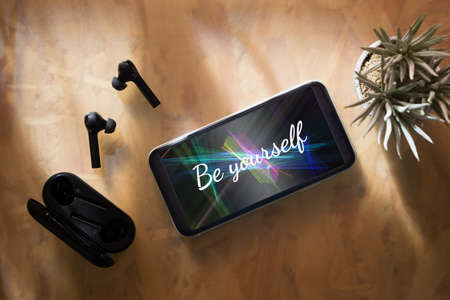Be yourself inspirational background concept. Flat lay top view of Be yourself text on Smartphone with Wireless earphones and charging case on wooden working office desk. Stockfoto