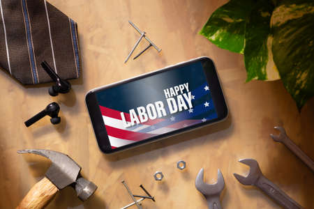 Happy labor day abstract background concept. Flat lay mockup smartphone with Happy Labor Day text and essential worker tools on businessman's working  wood table background.