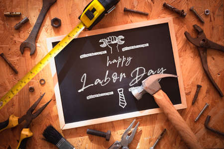 Happy Labor day background concept. Blackboard on wood with grunge and rusty  engineering handy tools arounds. Mockup chalkboard. Stockfoto
