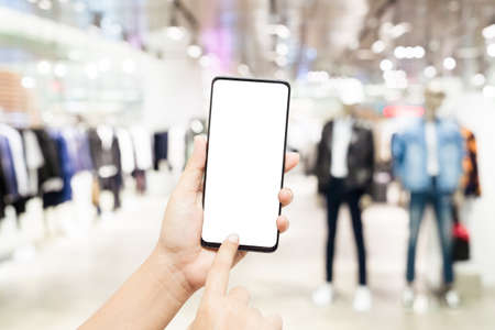 Mockup blank white screen mobile phone. Hand holding and pointing to smartphone wirh blurred male clothing store background for your text or advertisement artwork. Stockfoto